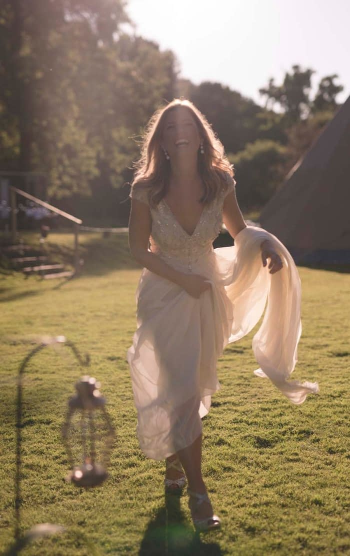 A back-lit bride enjoying her rustic wedding with brass lanterns on crooks at Busbridge Lakes, a UK wedding venue