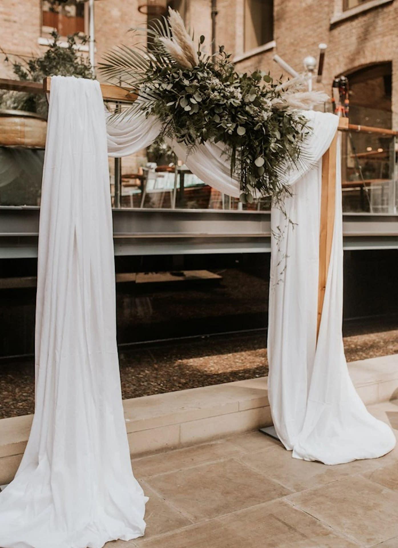 Muslin ceremony backdrop at Devonshire Terrace, London wedding venue