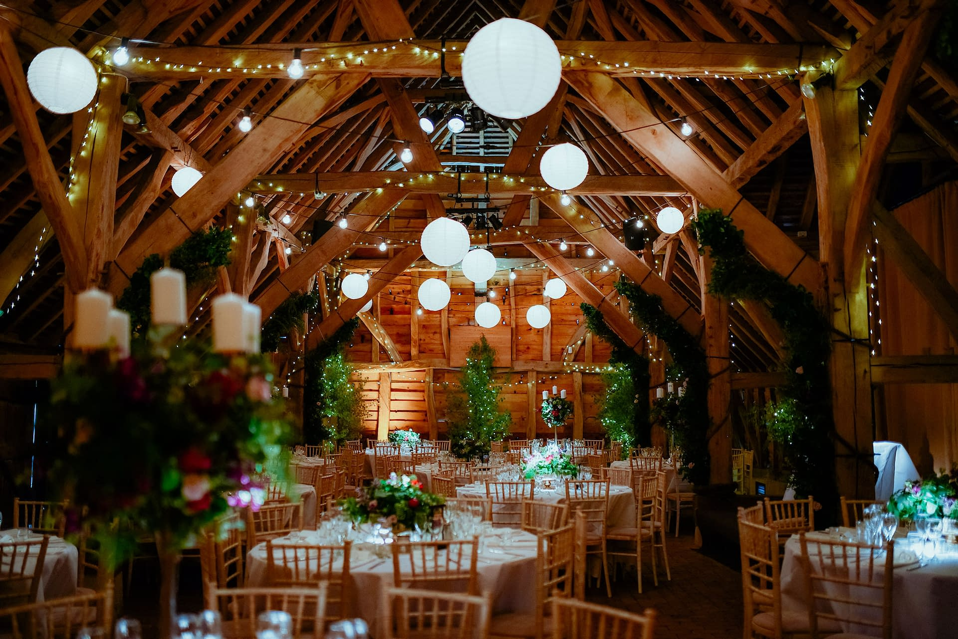 Overhead festoon lights with paper lanterns, birch trees with fairy lights and pinspot lights to the table centres at Gildings Barn, UK wedding venue