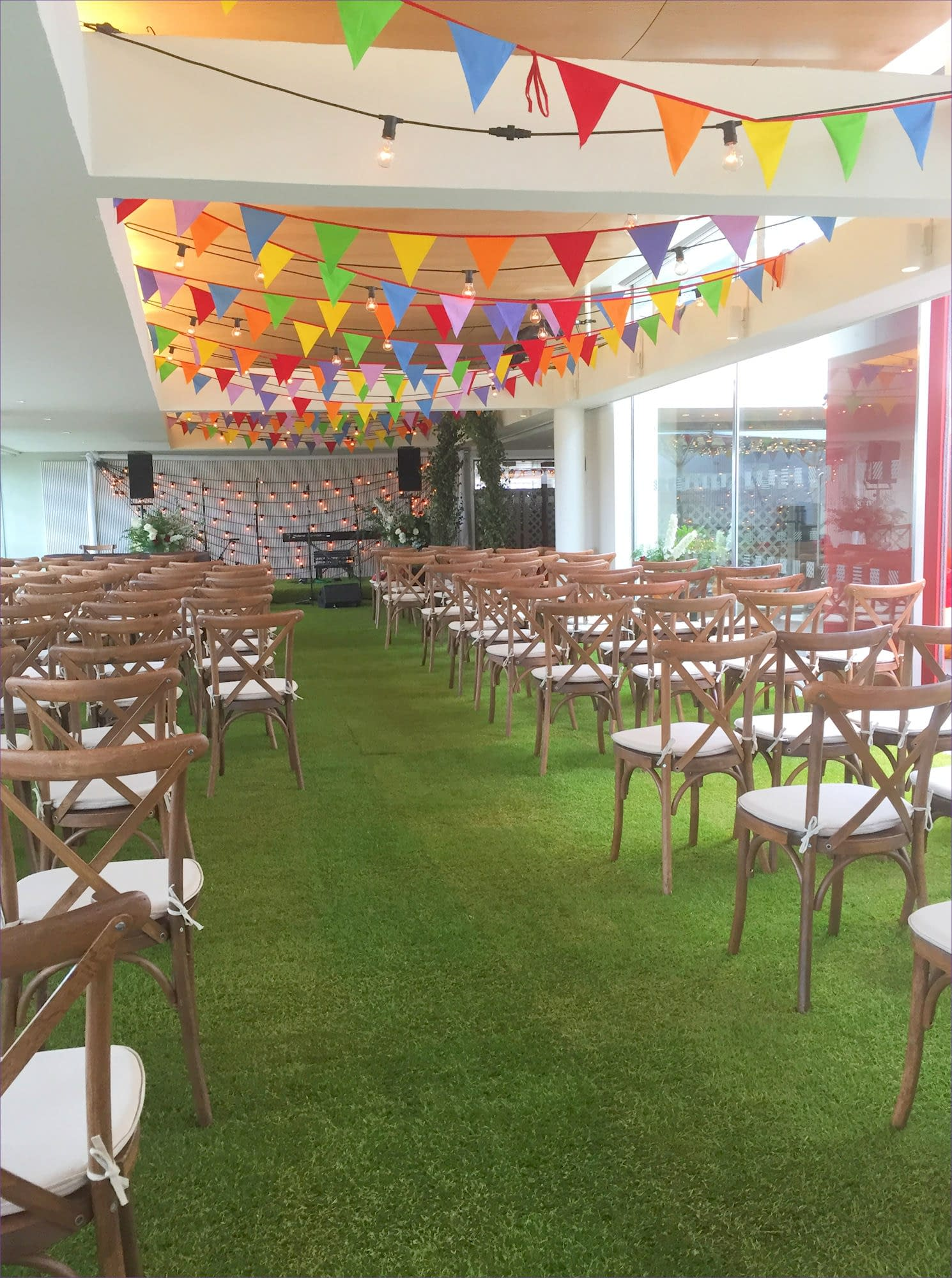 Festival themed wedding with colourful bunting, real grass and festoon lighting and rustic furniture at The Royal Festival Hall, London event venue