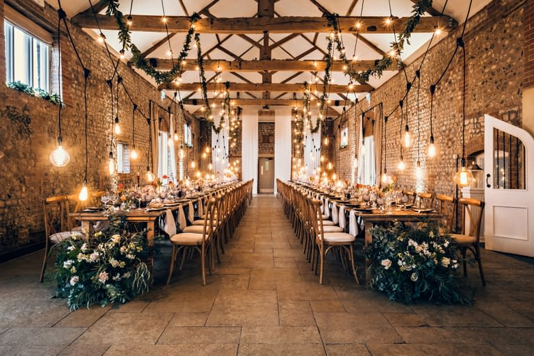 Swags of festoon lighting with retro filament drops plus foliage garlands over two long rows of rustic tables at Farbridge UK wedding venue