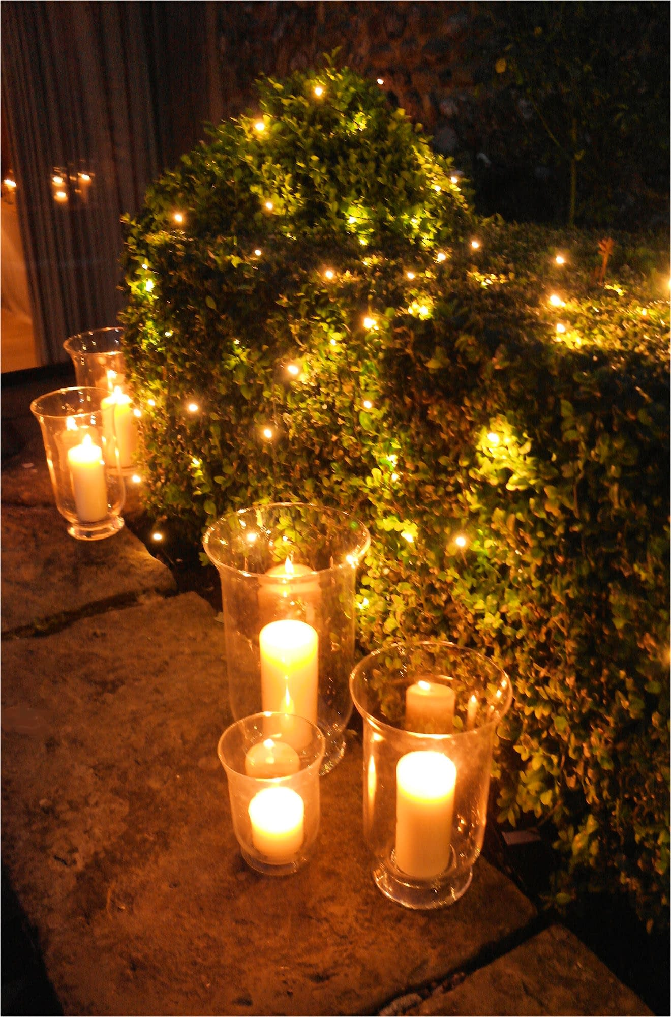 Fairy lights in bushes and storm lantern decoration at Chaucer Barn, UK wedding venue