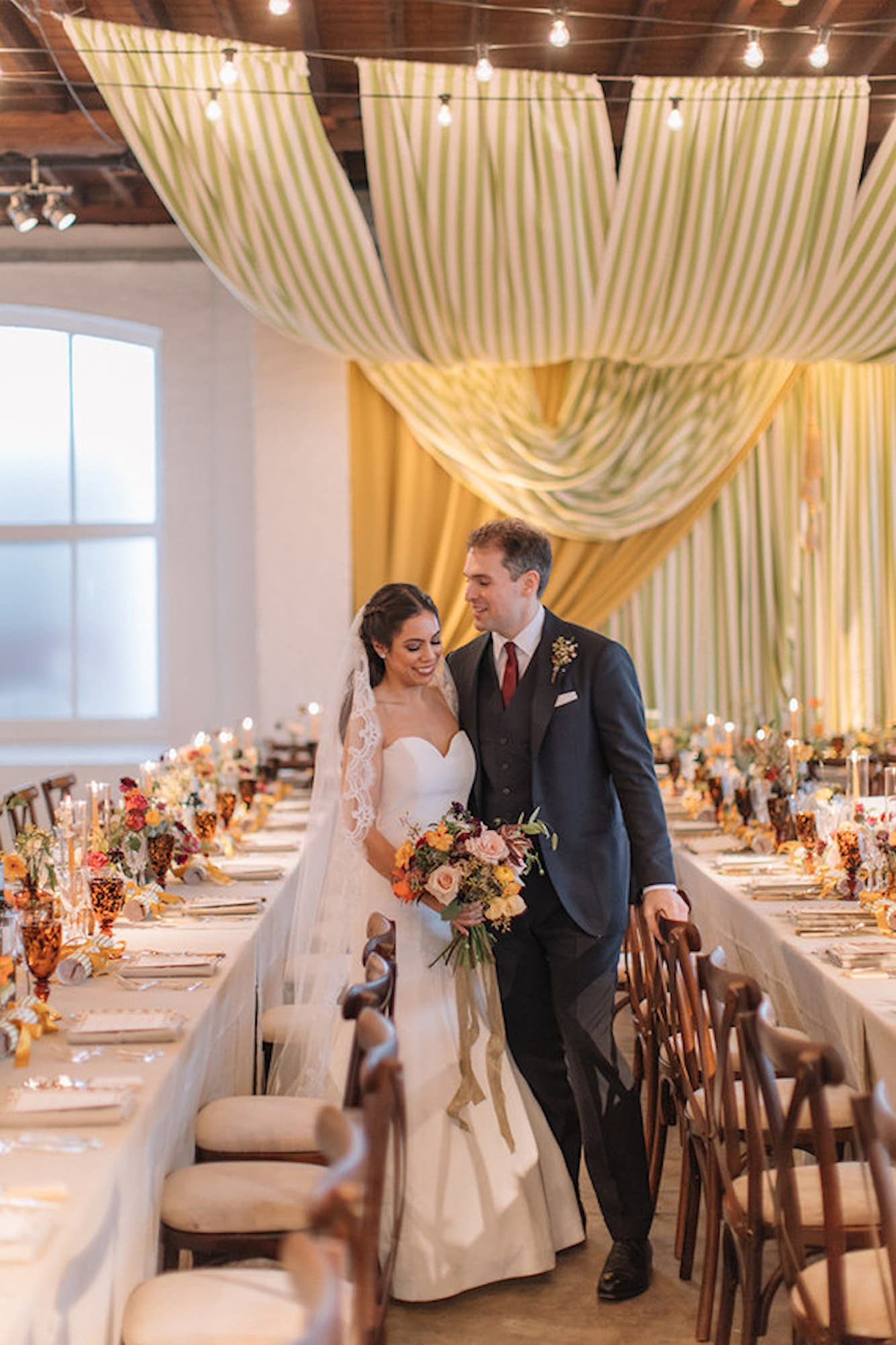 Bespoke wedding ceiling drapes and top table backdrop in green, white and mustard pictured with the bride and groom in the foreground