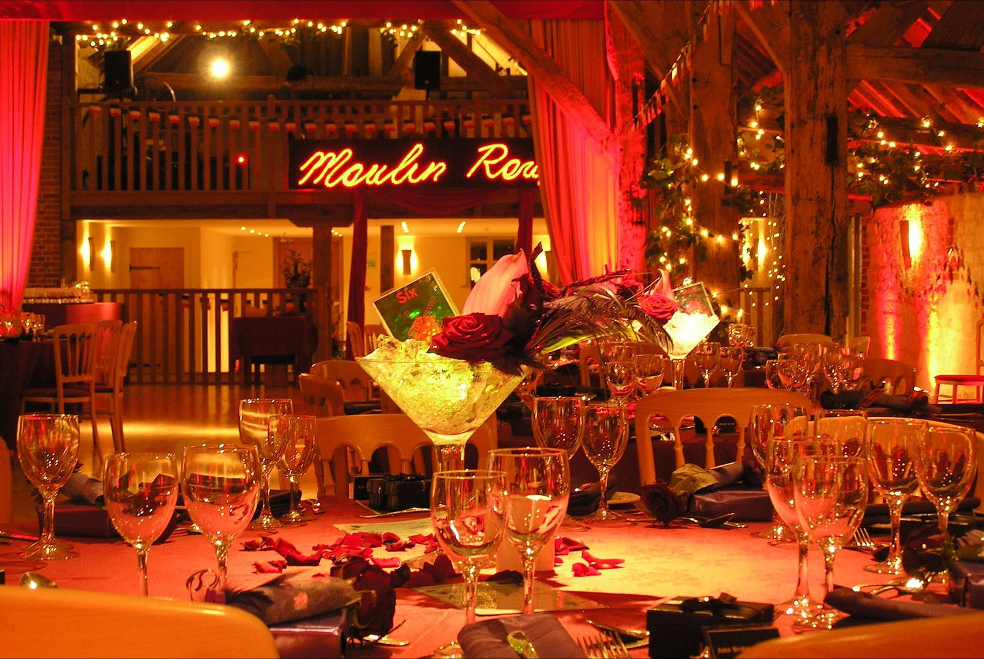 A Moulin Rouge themed party with mood lighting, illuminated sign, themed props and table centres at Bury Court Barn UK wedding venue supplied by event planning company Stressfree venue transformations