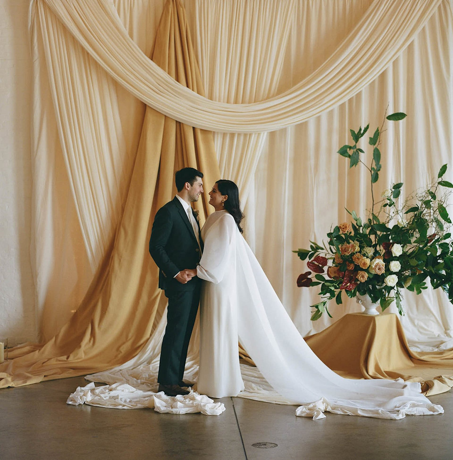 Interior design inspired bespoke wedding backdrop at Trinity Buoy Wharf London in natural fabrics with the bride and groom pictured in the foreground