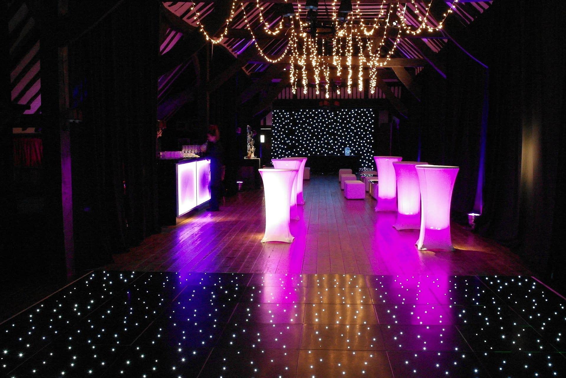 Starcloth backdrop, black wall draping, illuminated furniture and starlit dance floor at Ramster wedding venue UK