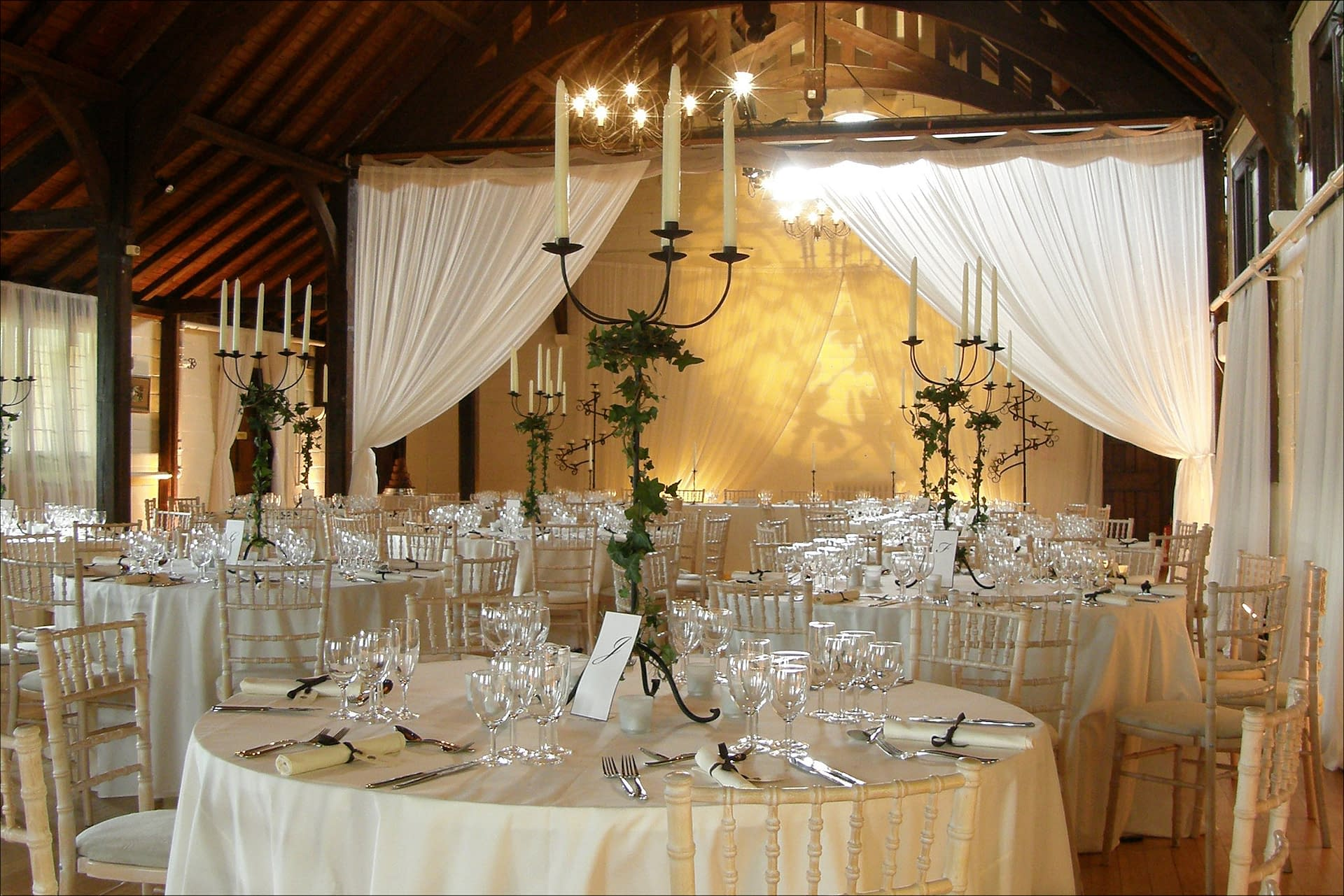 Partition drapes, subtle amber lighting plus floor-standing and table candelabra at Worfield Village Hall wedding venue UK