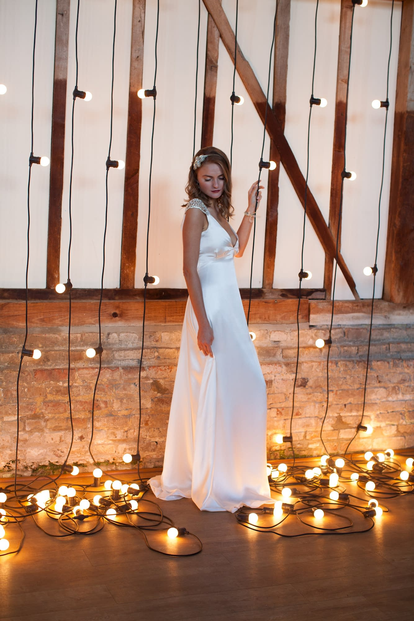 Festoon cascade at Bonhams Barn Hampshire England with bride standing in front of it surrounding by lightbulbs cascading and puddling on the floor