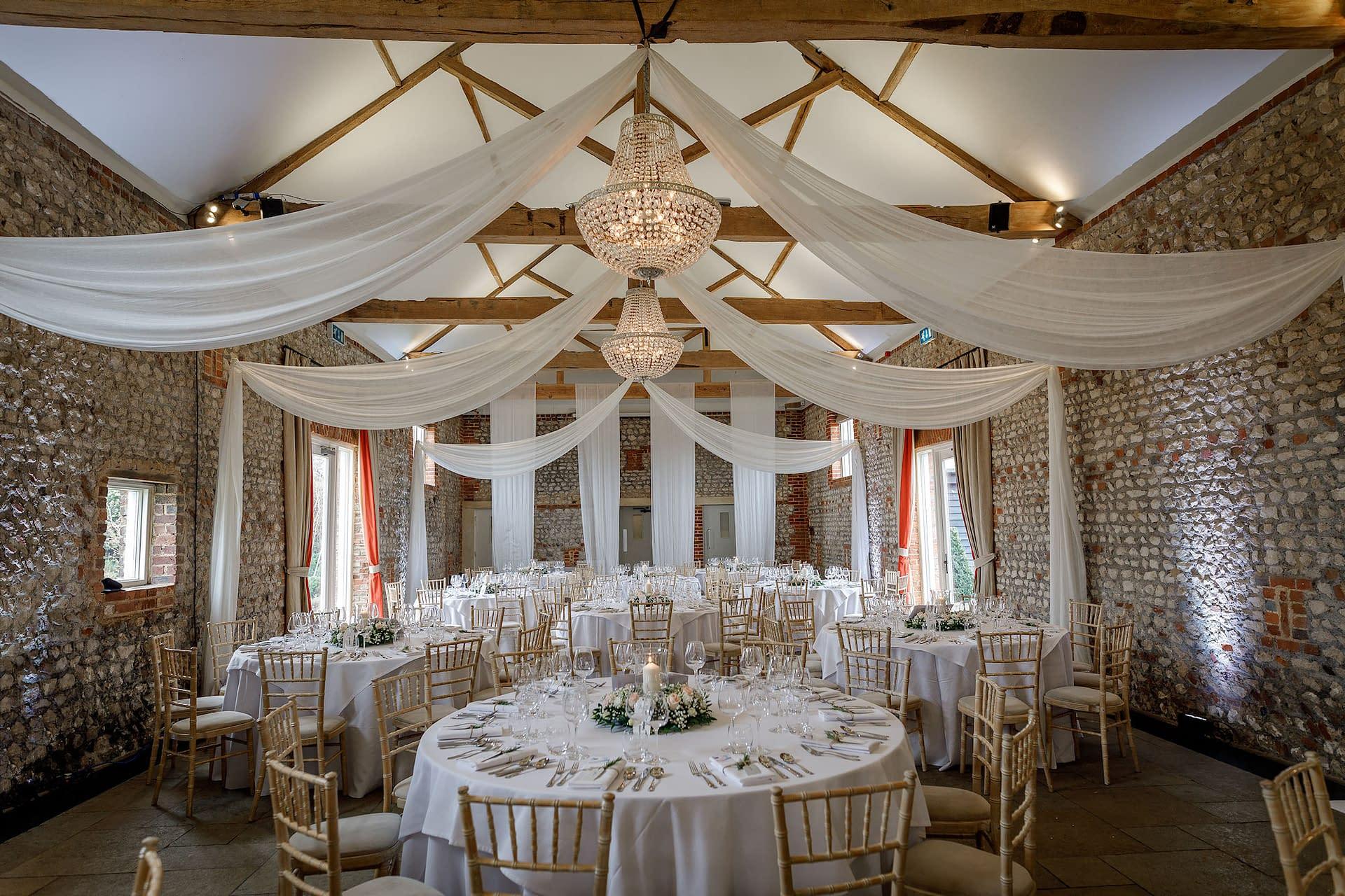 Muslin beam drapes with crystal swag chandeliers at Farbridge, UK wedding venue