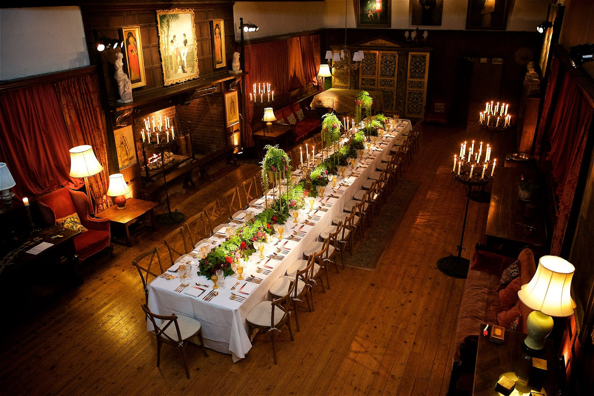 Floor standing carousel candelabra and fake fire insert with pinspots to the table and wall uplighting at Ramster Hall, UK wedding venue