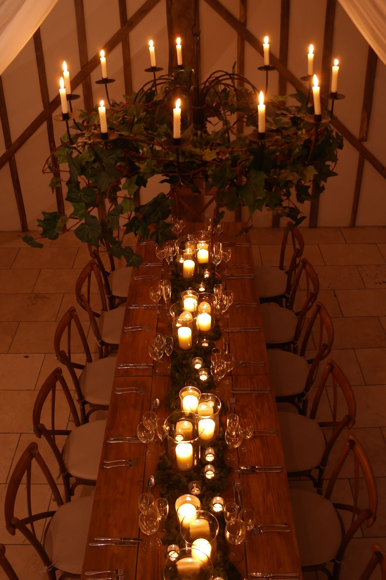 Rustic candlelit tablescape for a Sussex barn wedding with long table storm lanterns moss and overhead foliage chandelier