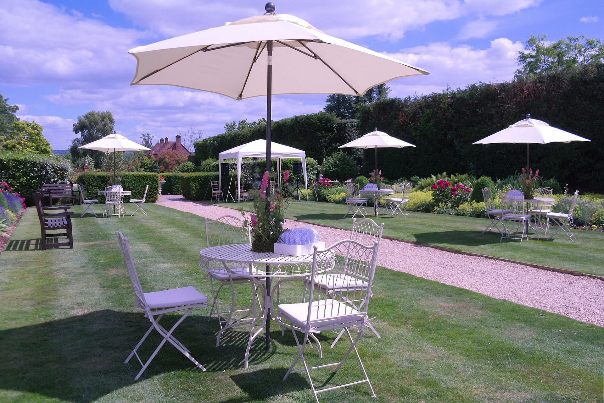 Vintage-style cream garden furniture with matching parasols at The Four Seasons Hotel, Hook, UK wedding venue