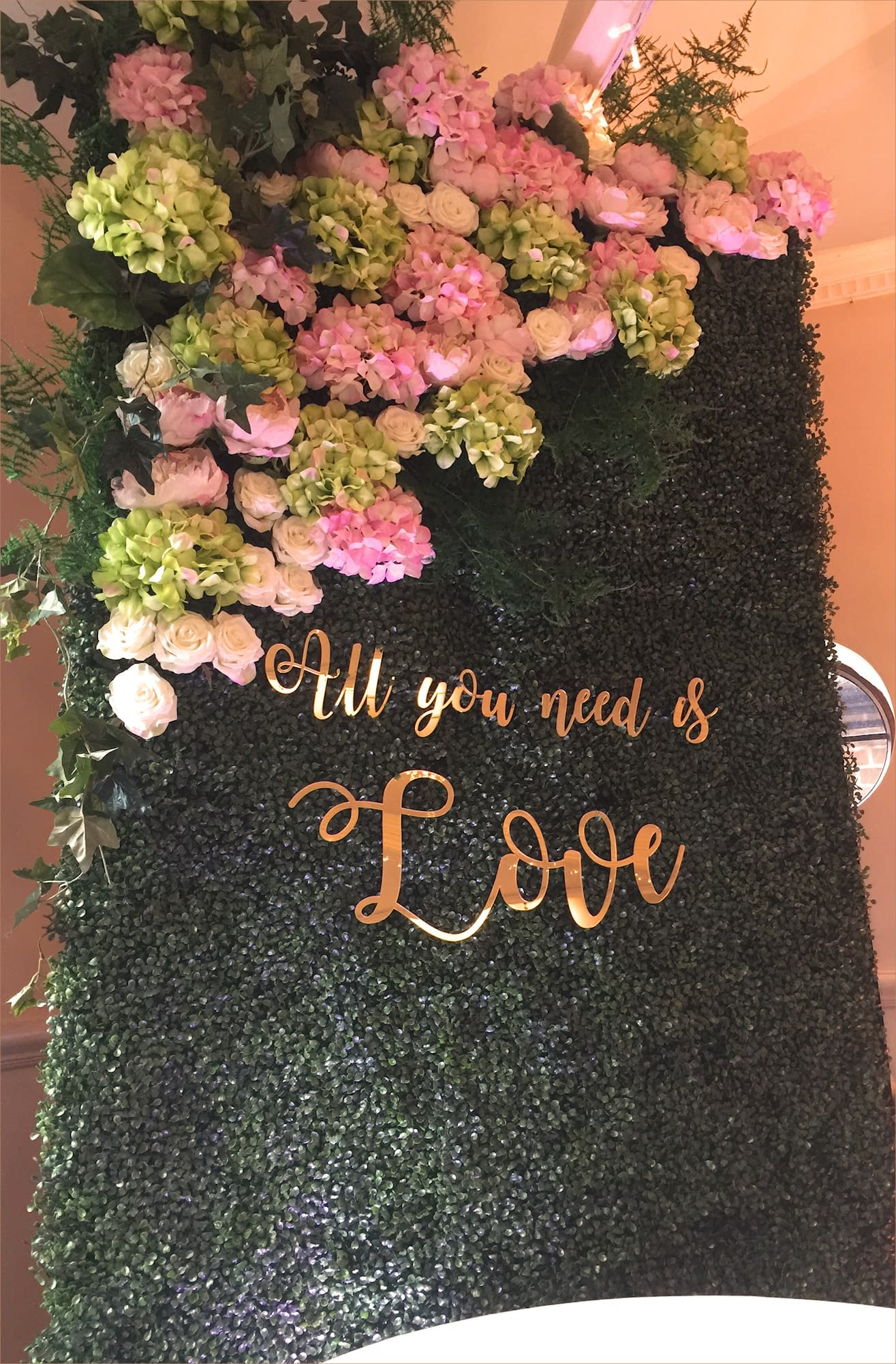 Box hedge photo backdrop with blush flowers to the top and all you need is love caption in gold