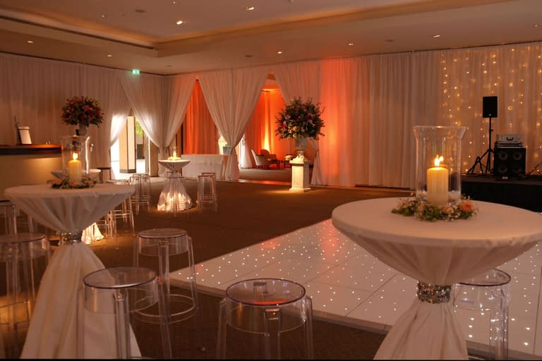 Ivory wall drapes with fairy light cascade, white starlit dancefloor, dressed poseur tables and mood lighting at The Hurlingham Club, London UK wedding venue