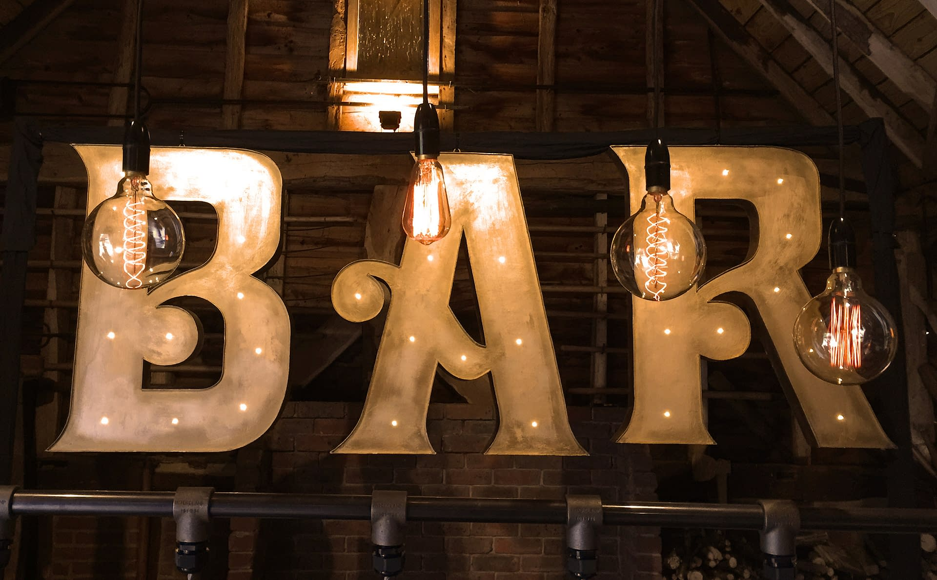 Large illuminated BAR letter props with retro filament lamps hung overhead at Gildings Barn in Surrey UK