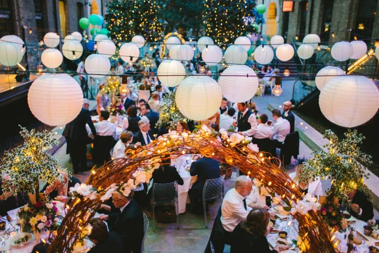 Overhead festoon lights with paper lanterns, twisted willow archways and fairy lights in the trees at Devonshire Terrace, London wedding venue