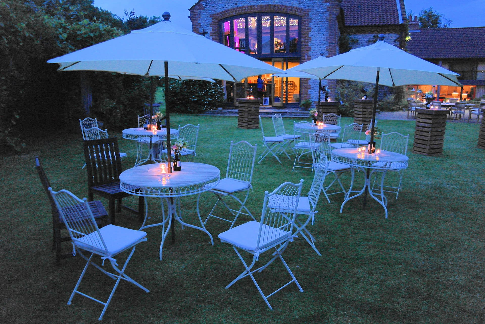 Vintage-style garden furniture and matching parasols, plus votive holders and fairy lights at Chaucer Barn, UK wedding venue