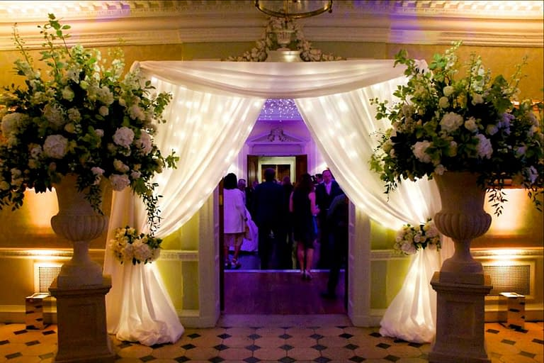 Wedding entrance décor using drapes with fairy lights at Hedsor House, UK wedding venue by Stressfree the venue dressers and wedding styling experts