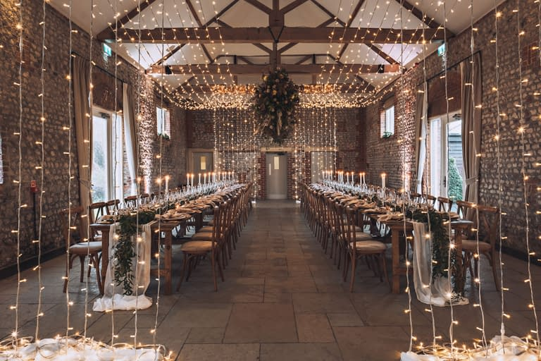Stunning double fairy light canopy with cascades at both ends over two long rows of rustic tables at Farbridge UK wedding venue
