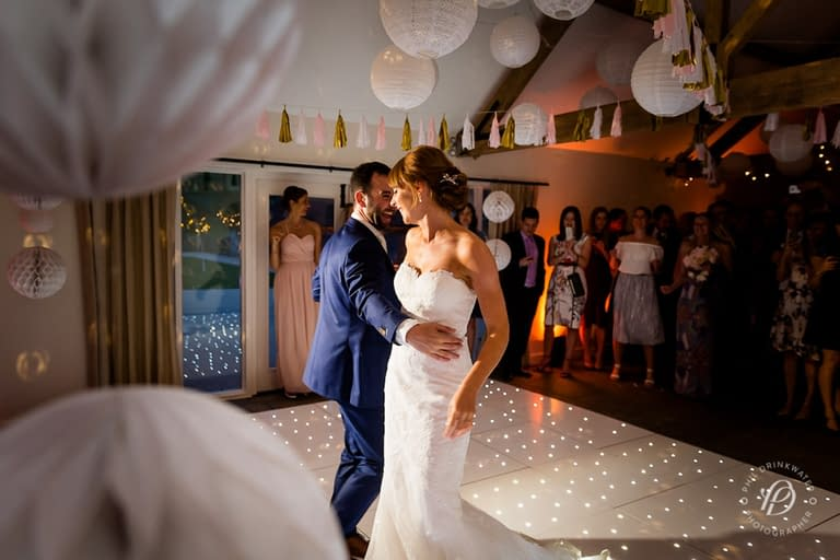 Paper and lace lanterns with pom-poms plus starlit dance floor and wall uplighters at Farbridge Barns, UK wedding venue