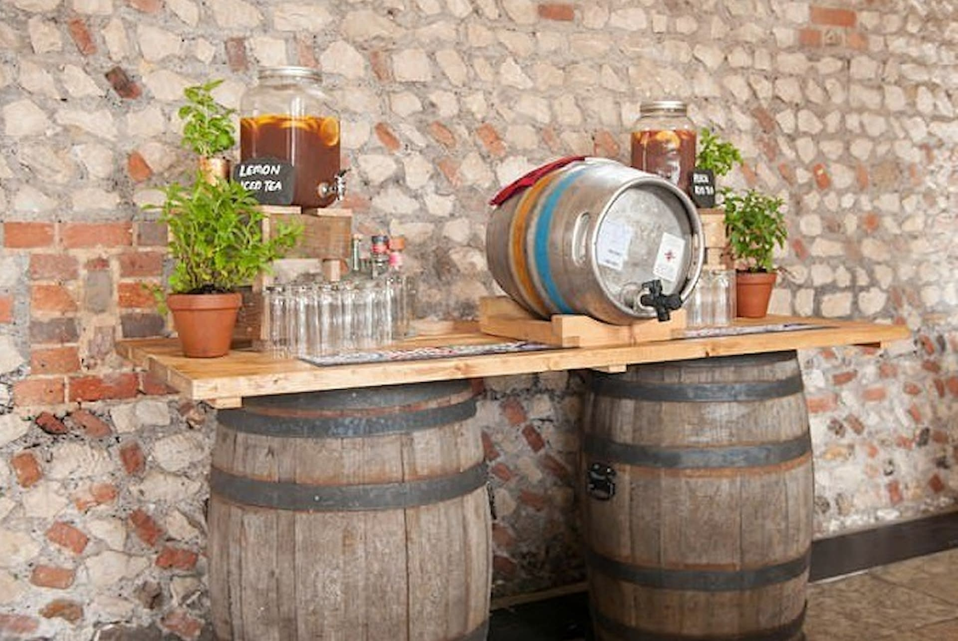 Country barn wedding at Farbridge Sussex with barrel bar prop dressed with beer barrel and pretty punch jars