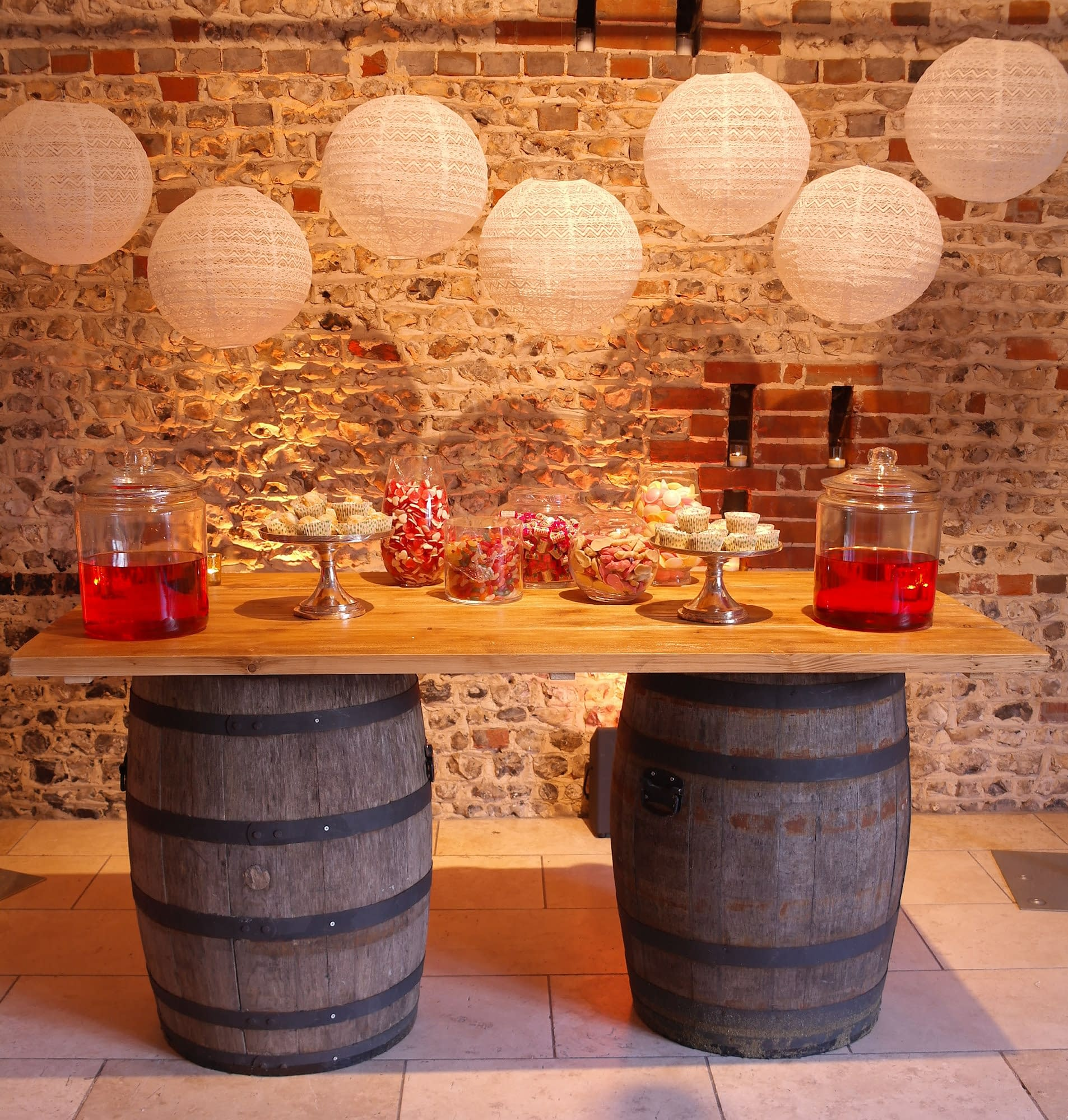 Rustic barrel bar for a sweet display with pretty lace lantern cluster overhead at Upwaltham Barns wedding venue Surrey