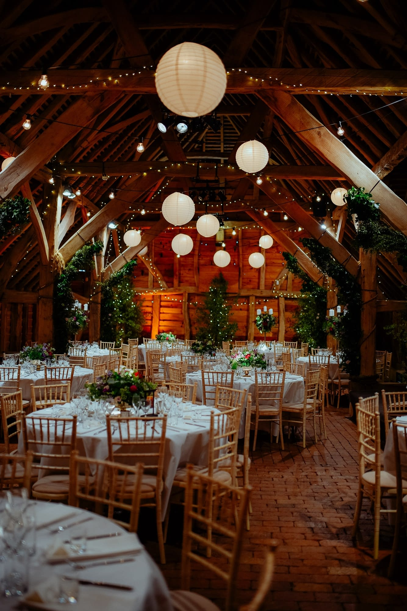 Overhead festoon lighting with paper lanterns, pinspot lights to table centres and birch trees with fairy lights at Gildings Farm, UK wedding venue