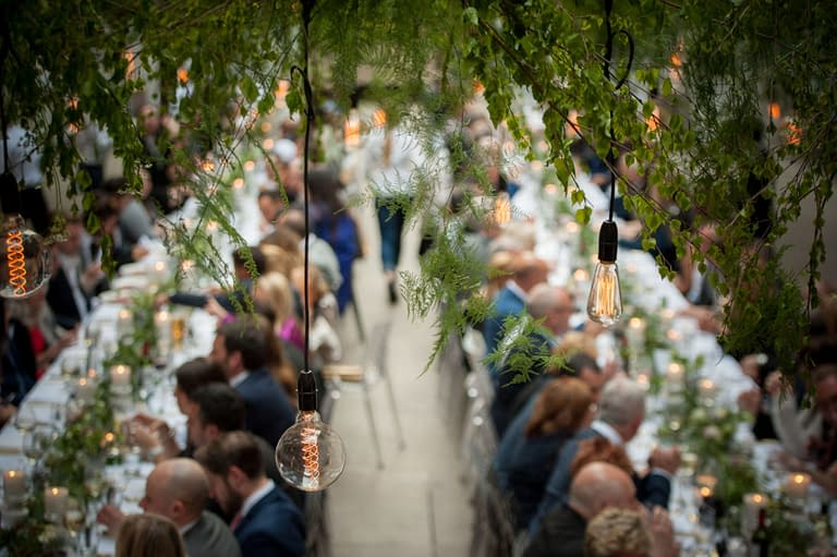 Overhead retro filament lamp drops dressed with foliage at Devonshire Terrace, a chic London wedding venue