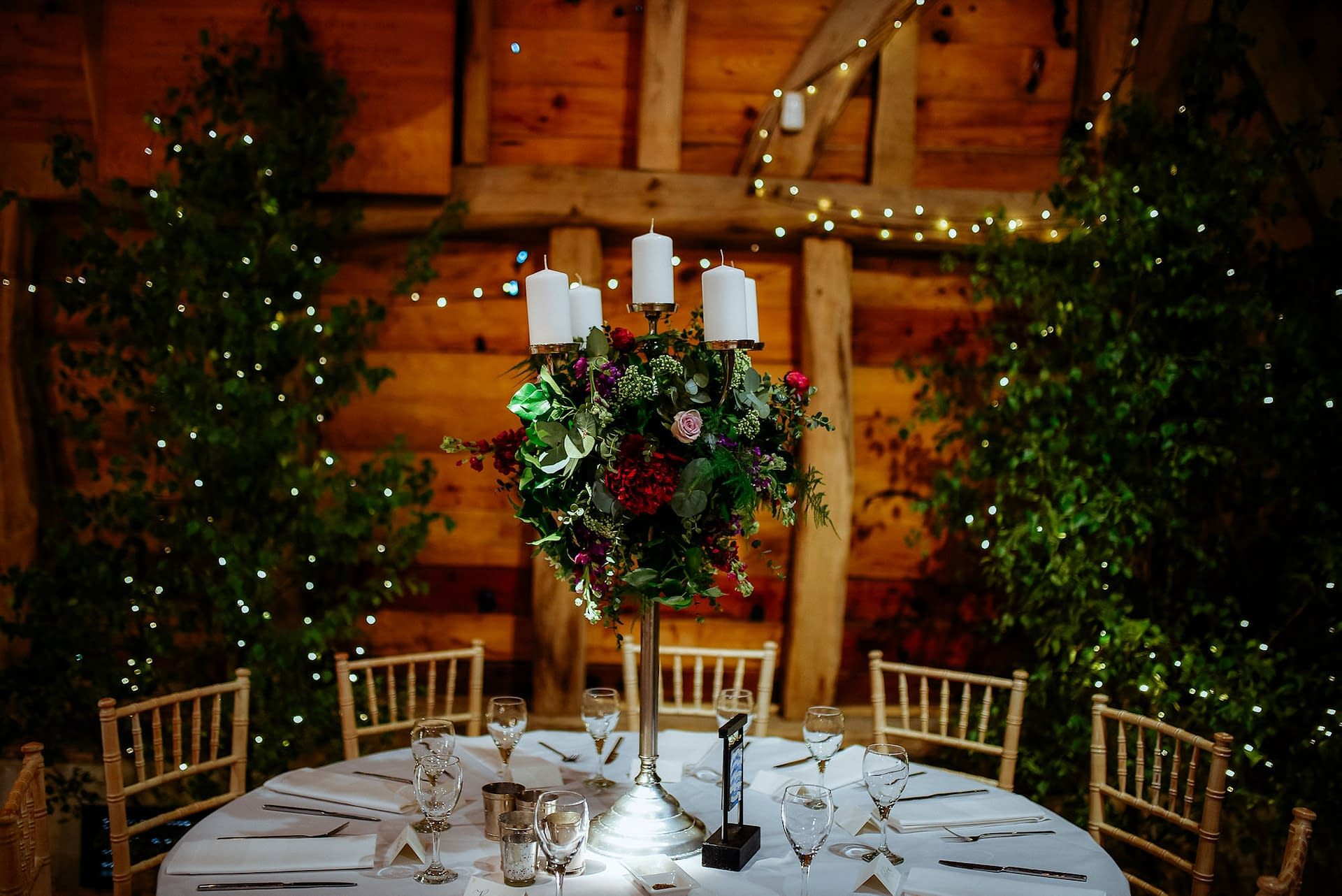 Birch trees, fairy lights and pinspot lights to table centres at Gildings Barn, UK wedding venue