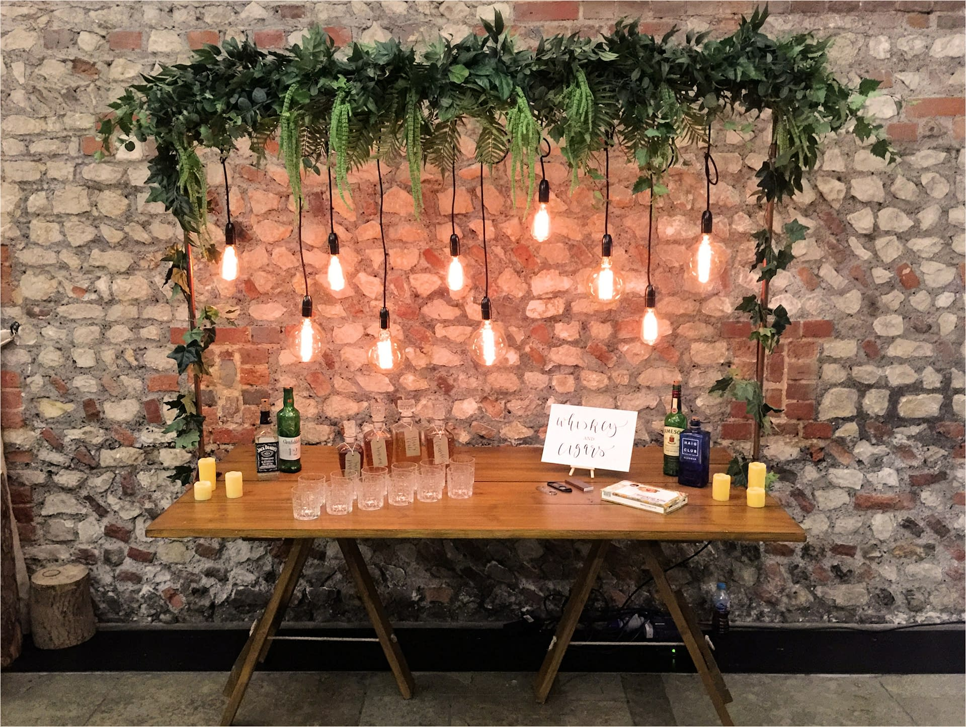 Fun rustic whisky bar styled using filament drops and foliage over a bare top table for a Sussex barn wedding at Farbridge