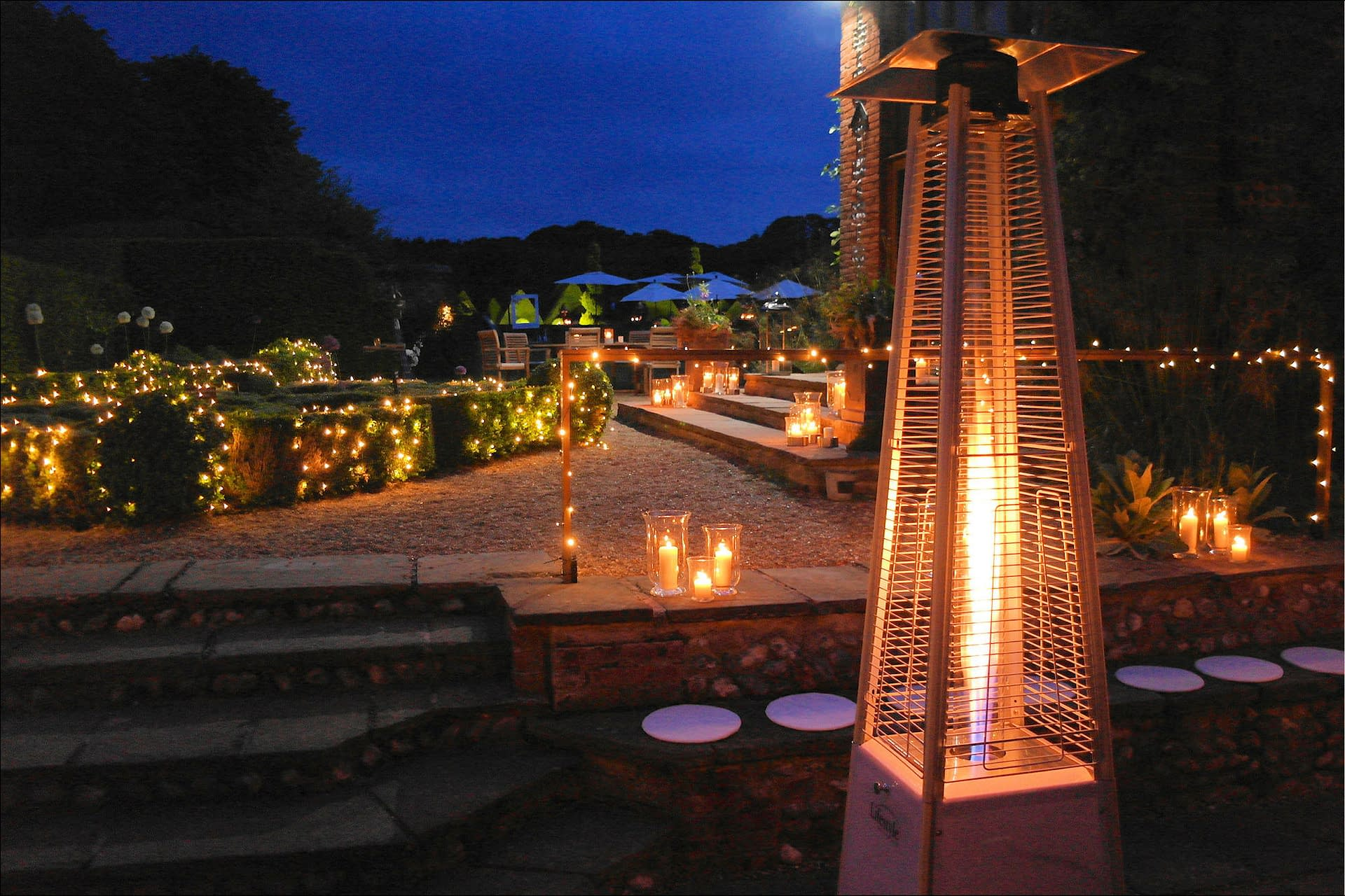 Fairy lights to dress the bushes plus storm lanterns, garden furniture and patio heaters at Chaucer Barn, a UK wedding venue