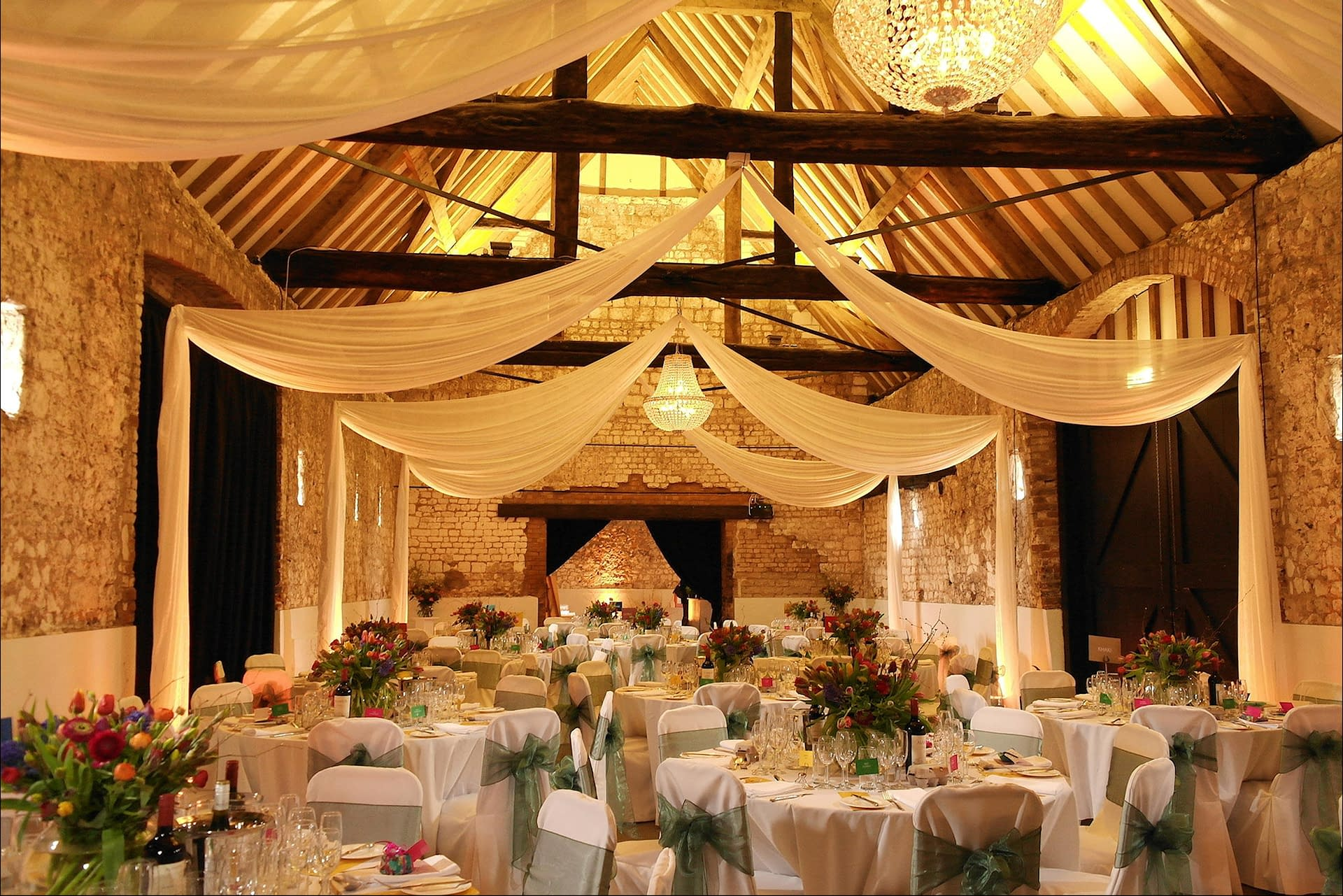 Ceiling swags with chandeliers and warm uplighting at Monks Barn wedding venue UK