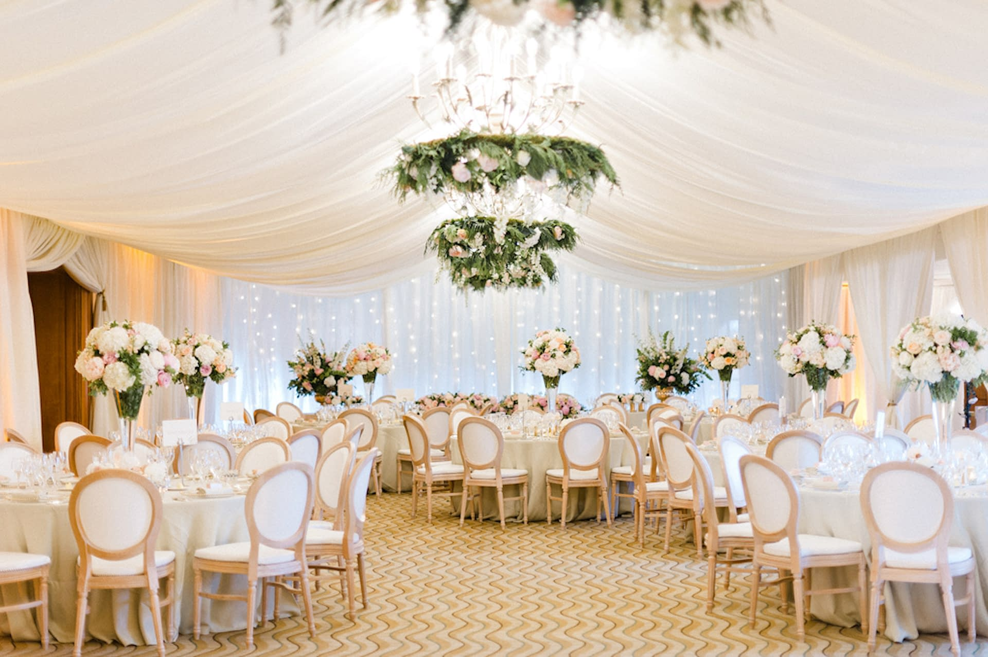 Wall and ceiling drapes with fairy light cascade and warm lighting supplied by Stressfree event planning company at Pennyhill Park wedding venue UK