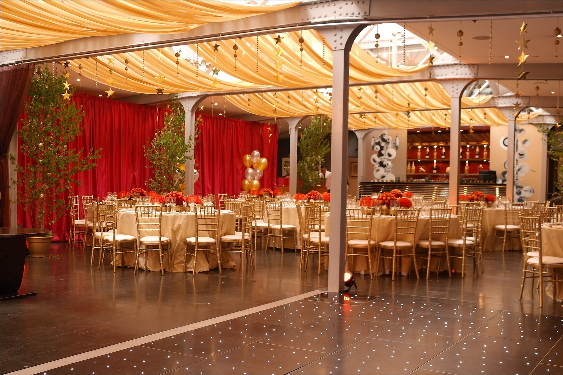 Gold ceiling drapes, birch trees with fairy lights, a starlit dance floor and warm mood lighting at The Bluebird Restaurant, UK party venue in Chelsea