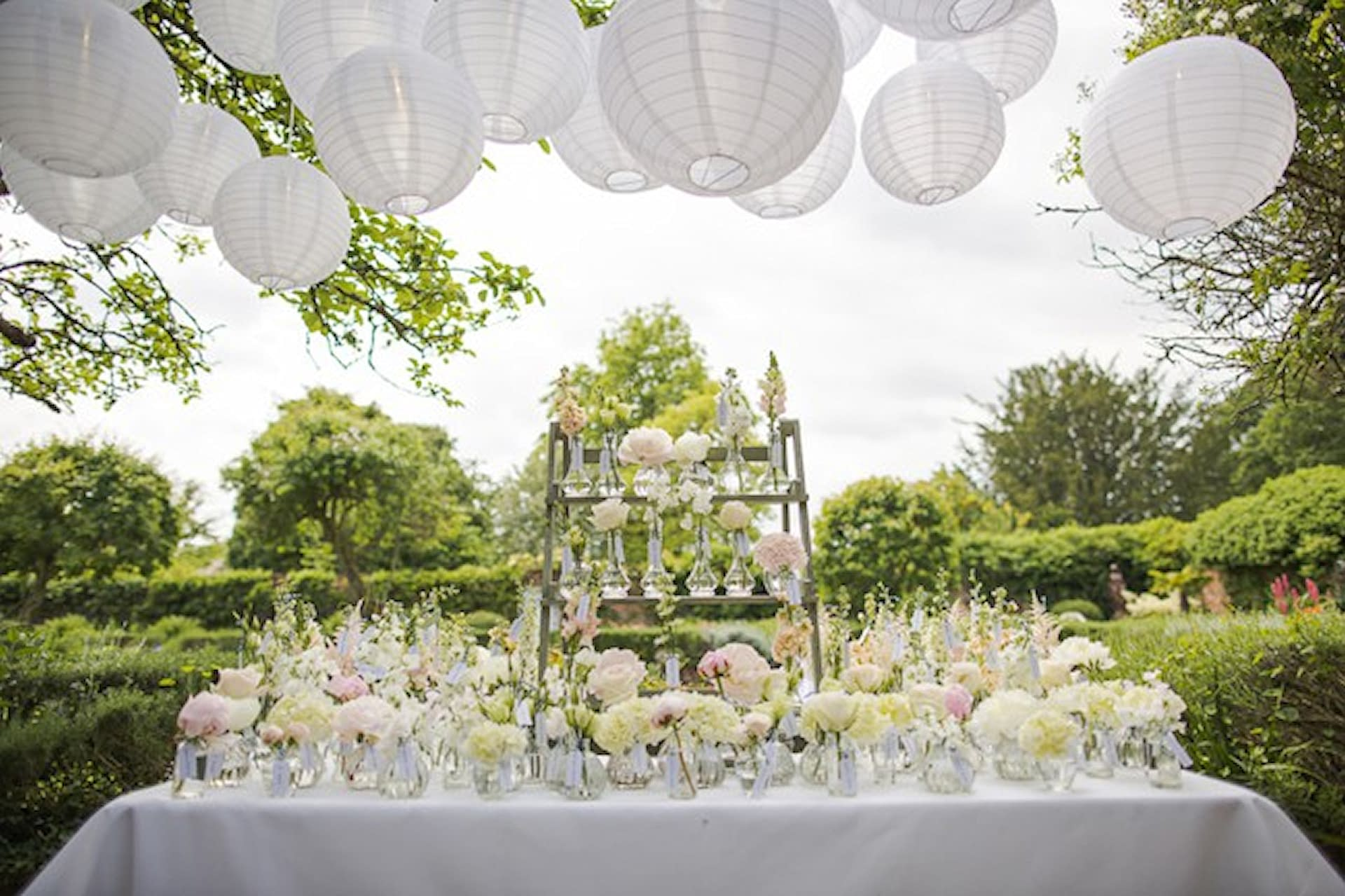 Pretty white paper lantern cluster set over a gorgeous floral tablescape for an outdoor garden wedding at Northbrook Park Surrey