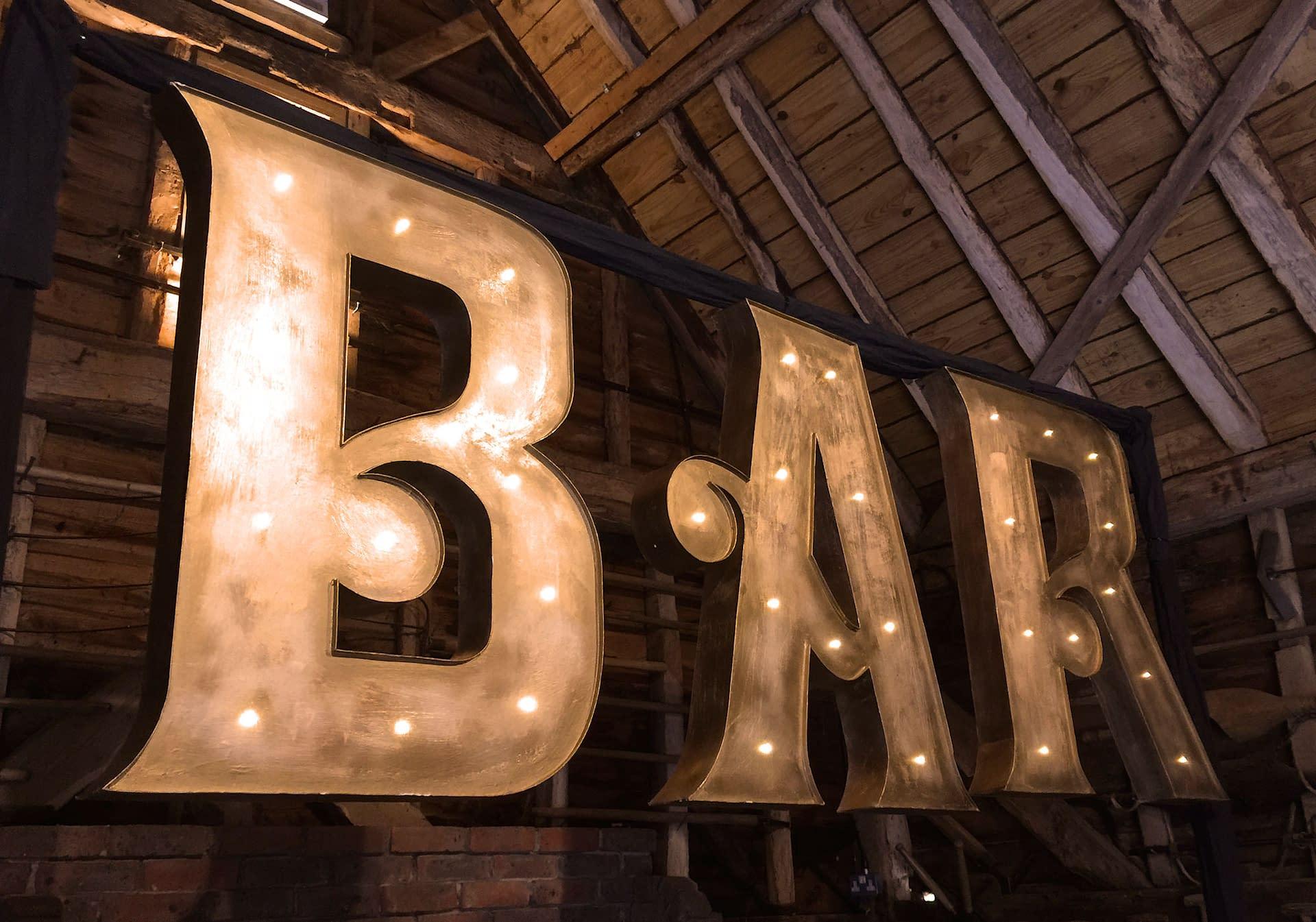 Large illuminated BAR letters in antique gold finish at Gildings Barn, UK wedding venue