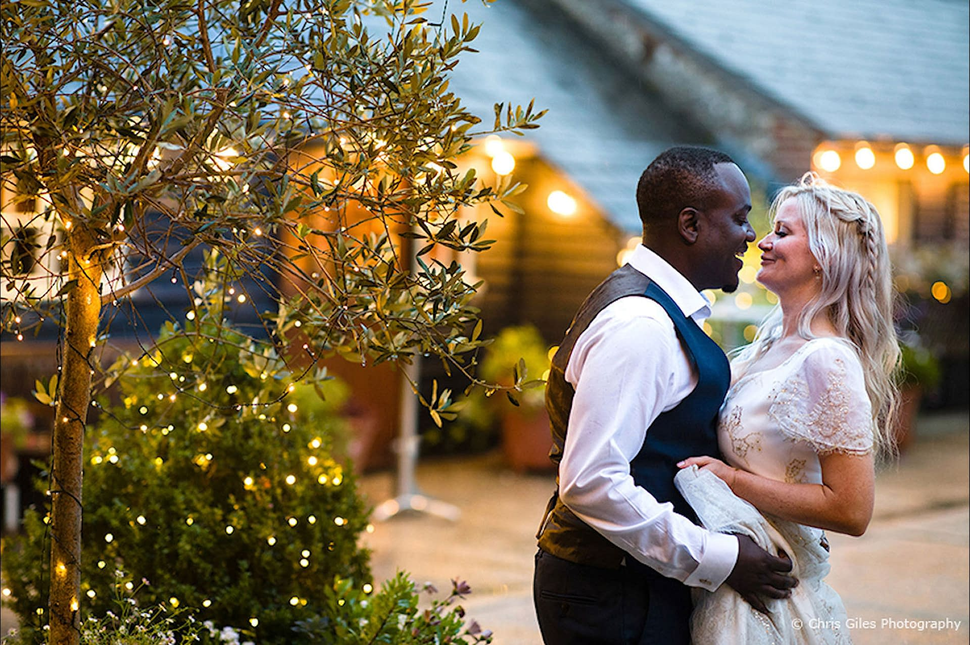 Outdoor wedding lighting using fairy lights for decorating trees and bushes in the courtyard at Upwaltham Barns, UK wedding venue