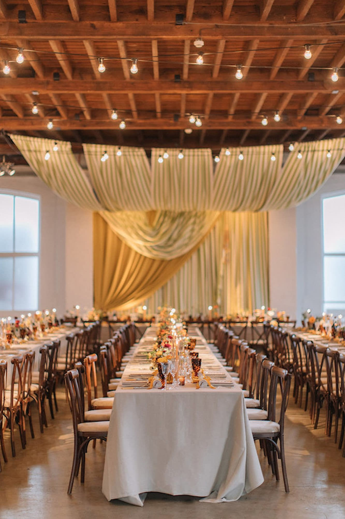 Bespoke top table backdrop with ceiling drapes in green white and mustard at Trinity Buoy Wharf wedding venue London