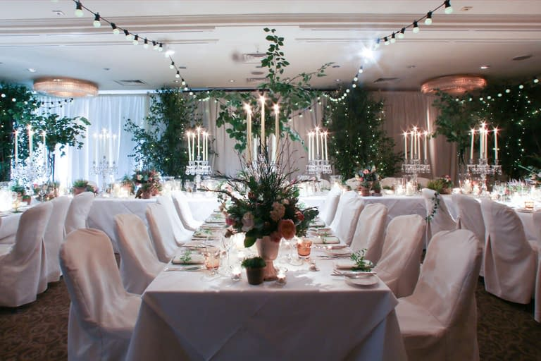 Overhead festoon lights, ivory wall drapes, crystal table candelabra and birch trees with fairy lights at Chewton Glen, a UK wedding venue